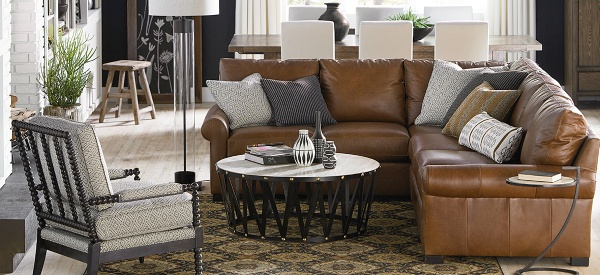 luxury living room featuring brown leather sofa with pillows, a brown diamond patterned area rug, round table, and off white patterned chair
