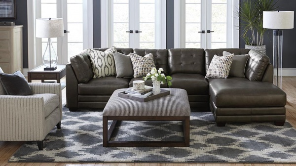 luxury living room featuring luxury leather sofa, diamond pattern area rug, and white striped chair