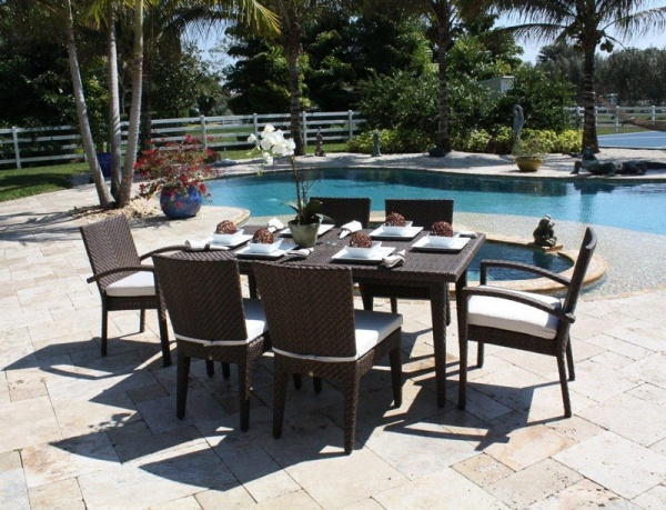 luxury patio including dark brown wicker outdoor dining table with six chairs next to the swimming pool
