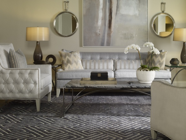 luxury living room featuring metallic silver couch with grey patterned rug with light grey chairs