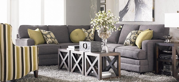 luxury living room featuring grey sofa with wooden tables and a striped olive and white chair