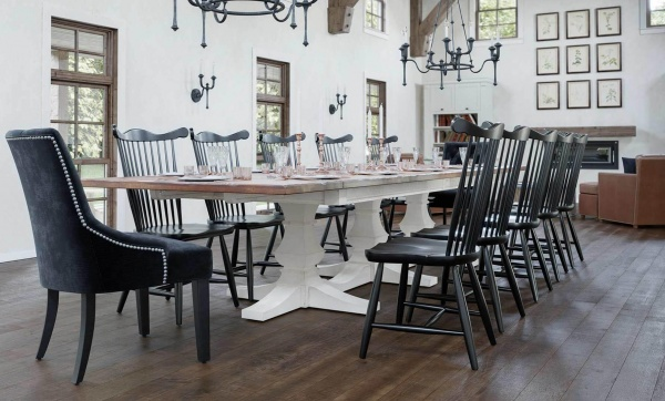 luxury dining room with large white wooden table with twelve black wooden chairs