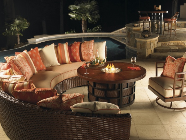 luxury patio including round wooden table, wicker wraparound outdoor sofa loaded with orange and cream pillows, with brown outdoor chair