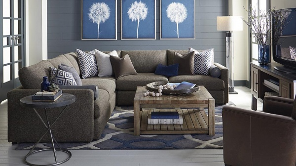 luxury living room with a blue color scheme including a brown couch with pillows, a wooden table, and brown leather chair