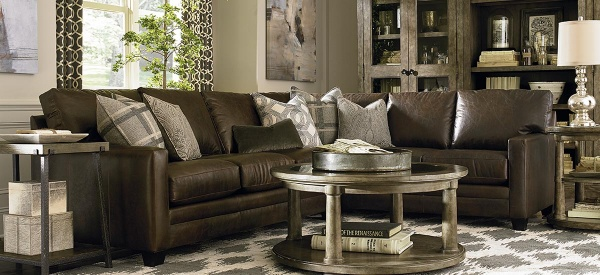 luxury living room featuring wraparound brown leather sofa with round wooden table with diamond patterned area rug