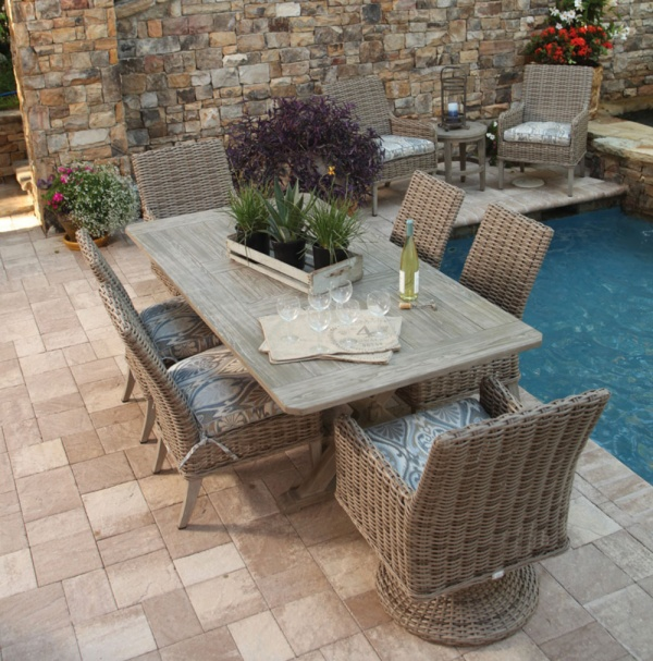 luxury patio including wood and wicker outdoor dining set, with a bottle of wine ready to be poured