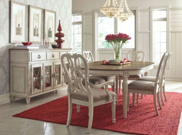 luxury dining room with light brown antiqued dining room table with 6 chairs and red area rug and accents