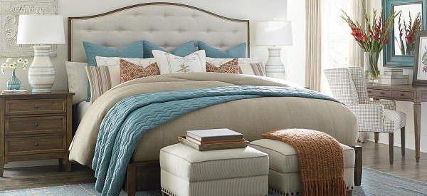 luxury home furniture bedroom with light blue, white, and rust colored bedding with brown furniture and white ottomans