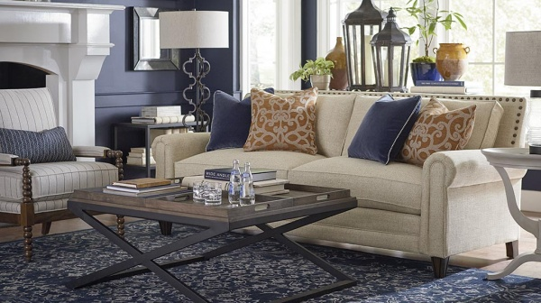 luxury living room featuring a blue and white color scheme with tan couch, white striped chair and wooden coffee table