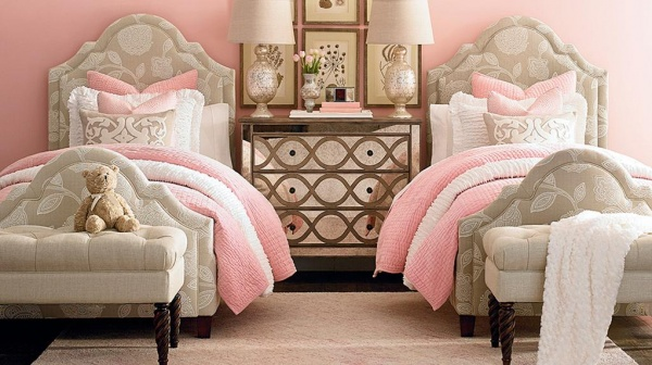 luxury finished interior bedroom with two beds with tan, white and pink color scheme with tan ottomans and brown wood nightstand
